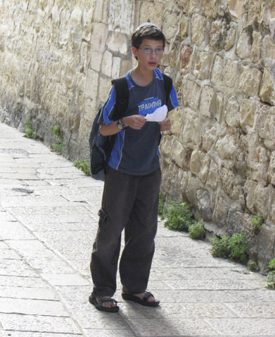 Young boy going to school with paper in hand